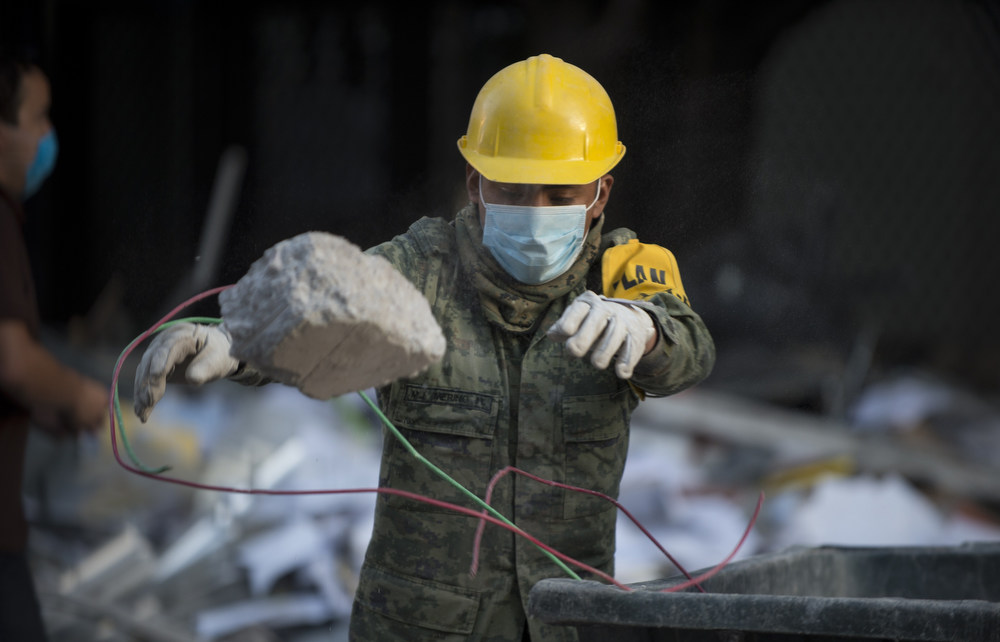 Description of . Mexican soldiers remove debris from the headquarters of the state-owned Mexican oil giant Pemex in Mexico City on February 1, 2013, following a blast inside the building. An explosion rocked the skyscraper, leaving up to now 25 dead and 100 injured, as a plume of black smoke billowed from the 54-floor tower, according to official sources.  AFP PHOTO/ YURI CORTEZ/AFP/Getty Images