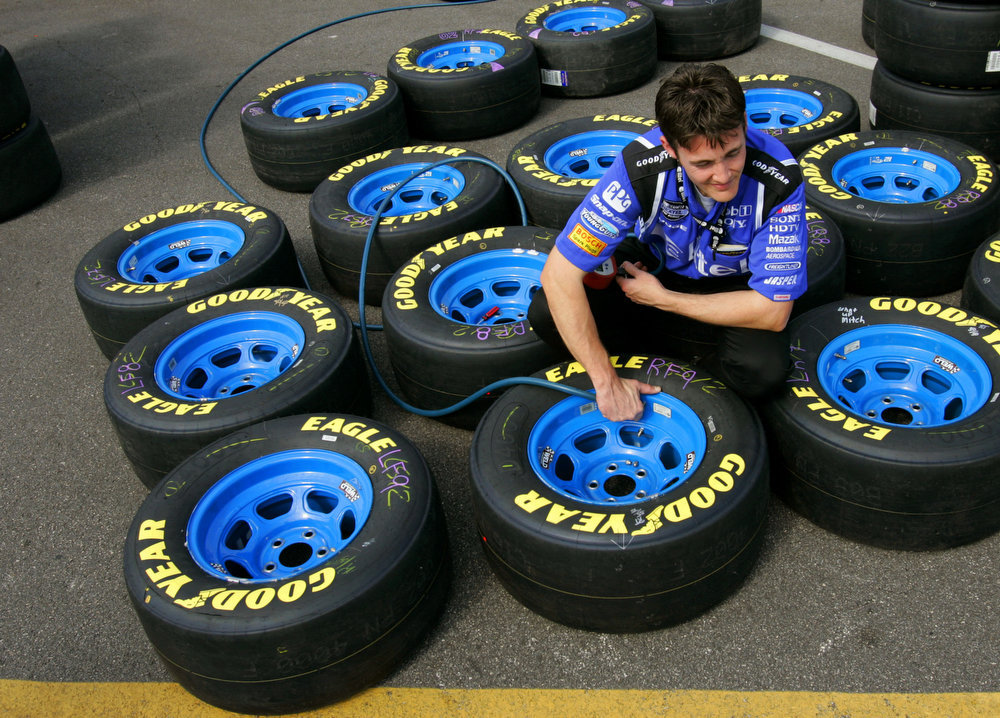 Description of . Lawrence Burch puts air in tires for the car driven by Ryan Newman following a practice for the NASCAR Daytona 500 auto race at Daytona International Speedway in Daytona Beach, Fla. Saturday, Feb. 11, 2006. (AP Photo/Lynne Sladky)