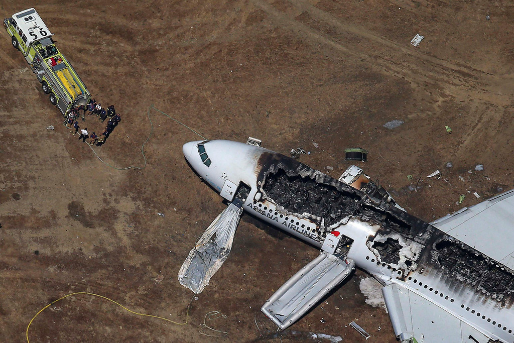 . Rescue officials stand near an Asiana Airlines Boeing 777 plane after it crashed while landing at San Francisco International Airport in California on July 6, 2013. Two people were killed and 130 were hospitalized after the plane crash-landed at San Francisco International Airport on Saturday morning, San Francisco Fire Department Chief Joanna Hayes-White said. The Boeing 777, which had flown from Seoul, South Korea, was carrying 307 people.  REUTERS/Jed Jacobsohn