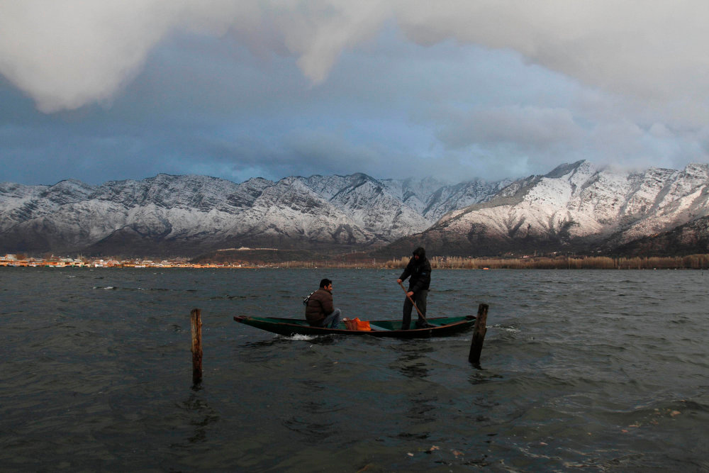 . Kashmiri fishermen row their boat during heavy winds on a rainy day at the Dal Lake in Srinagar, India, Tuesday, Feb. 5, 2013. (AP Photo/Mukhtar Khan)