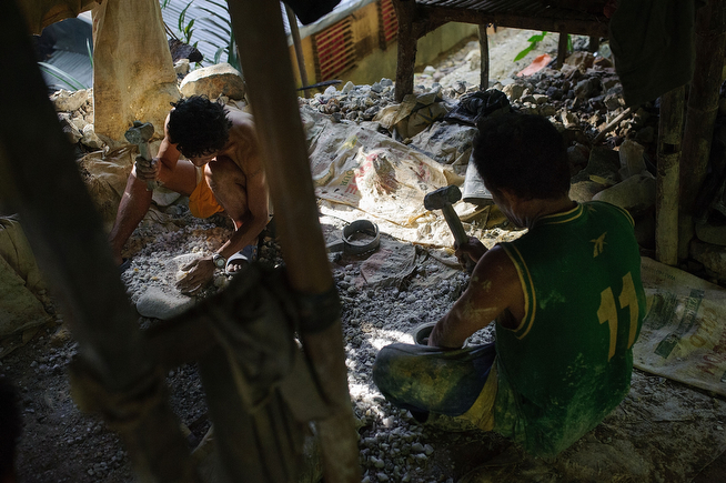 . Miners break large rock fragments into more manageable pieces using sledgehammers and anvil stones, on April 22, 2014 in Pinut-An, Philippines. (Photo by Luc Forsyth/Getty Images)