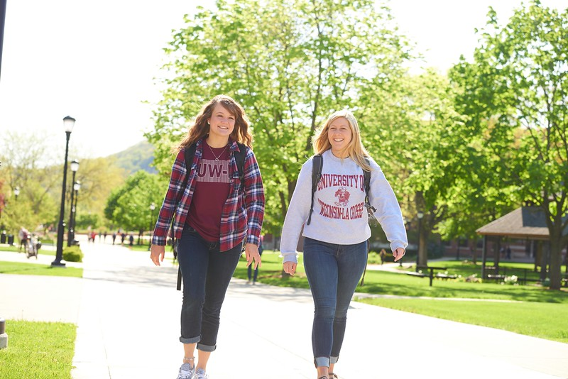 Activity; Walking; Smiling; Buildings; Location; Outside; People; Woman Women; Student Students; Spring; May; Time/Weather; sunny; Type of Photography; Candid; Lifestyle; UWL UW-L UW-La Crosse University of Wisconsin-La Crosse; Emma Hermes