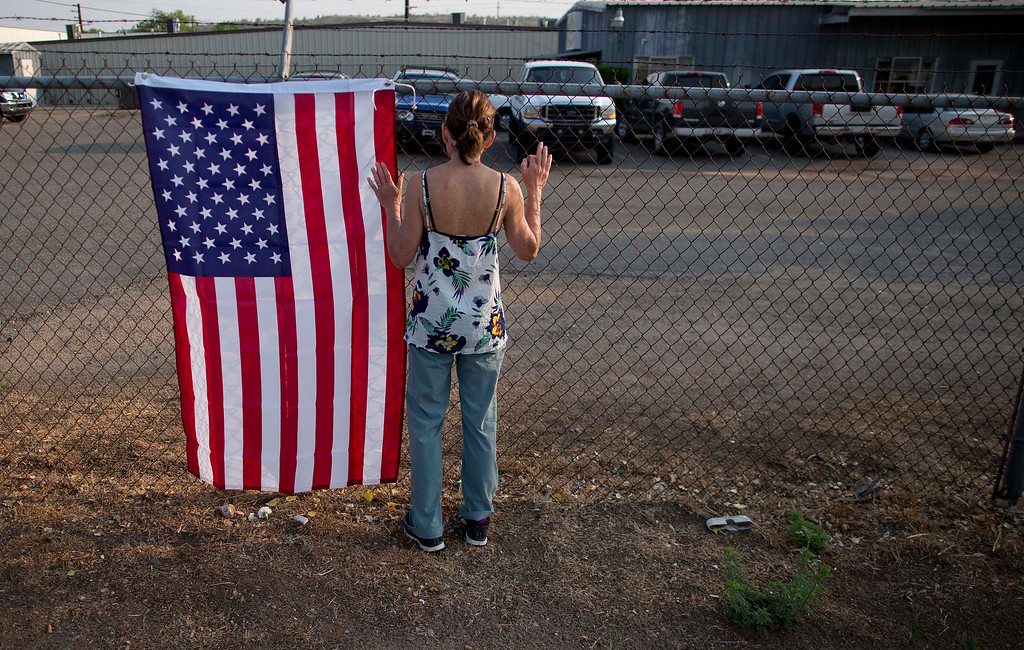 . Toby Schultz pauses after laying flowers at the gate of the Granite Mountain Hot Shot Crew fire station, Monday, July 1, 2013, in Prescott, Ariz.  (AP Photo/Julie Jacobson)