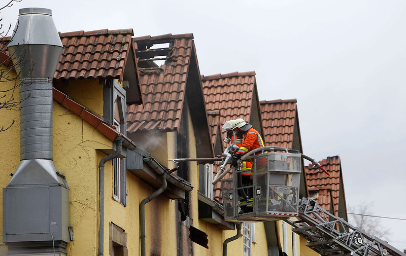 . Fire fighters work on a damaged roof following a fire in Backnang March 10, 2013. At least eight people, including seven children, died after a fire broke out in an apartment building in the southern German province of Baden-Wuerttemberg on Sunday. The cause of the fire is not yet known. REUTERS/Lisi Niesner