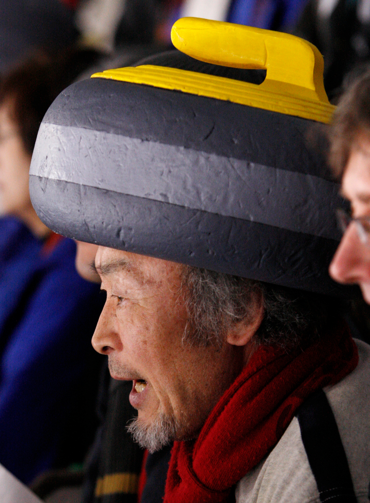 . A fan wears a curling stone hat while watching the Japanese team at women\'s curling at the Vancouver 2010 Olympics in Vancouver, British Columbia, Monday, Feb. 22, 2010. (AP Photo/Robert F. Bukaty)