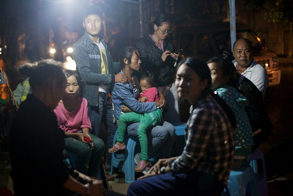 . This picture taken on August 3, 2014 shows earthquake victims sitting by the street side at night in Ludian county, part of Zhaotong, in southwest China\'s Yunnan province.  More than 367 people died and nearly 2,000 were injured when a strong earthquake hit southwest China\'s mountainous Yunnan province on August 3, bringing homes crashing to the ground and sparking a massive relief operation.   STR/AFP/Getty Images
