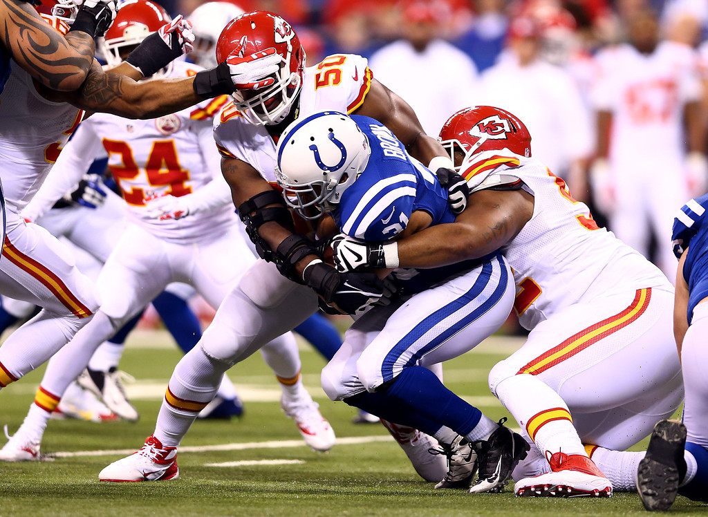 . INDIANAPOLIS, IN - JANUARY 04: Running back Donald Brown #31 of the Indianapolis Colts is tackled by outside linebacker Justin Houston #50 of the Kansas City Chiefs during a Wild Card Playoff game at Lucas Oil Stadium on January 4, 2014 in Indianapolis, Indiana.  (Photo by Andy Lyons/Getty Images)