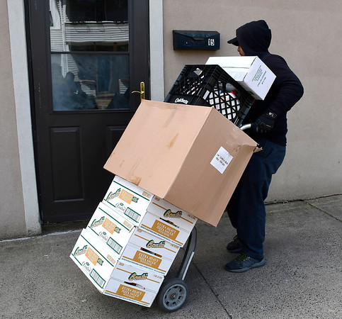 4/2/2020 Mike Orazzi | Staff Napoli Foods' Angel Santana delivers food to West End Pizza in Bristol on Thursday.