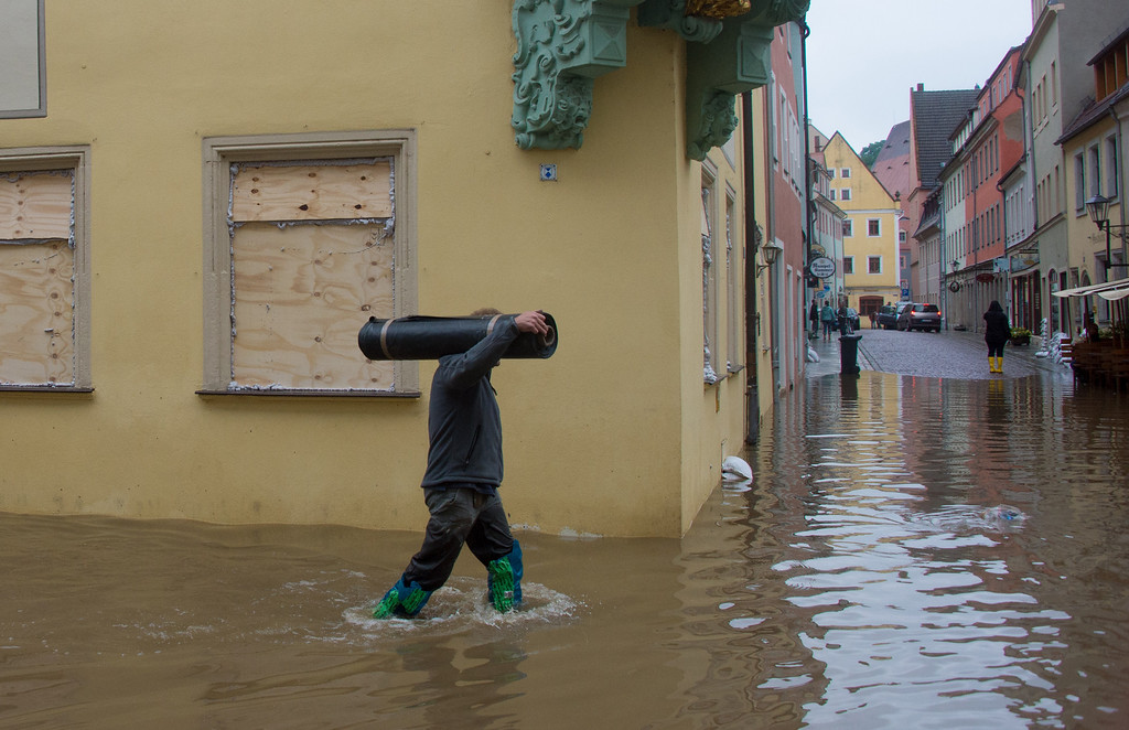 . A man walks through a street submerging in the floods of the river Elbe in Pirna, eastern Germany, on June 4, 2013. German Chancellor Angela Merkel pledged 100 million euros ($130 million) in emergency aid for flood-ravaged areas, as surging waters that have already claimed 10 lives and forced tens of thousands of evacuations across Europe bore down towards Germany.  JOHANNES EISELE/AFP/Getty Images