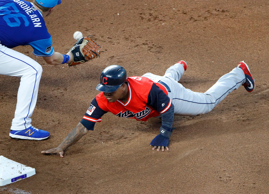 . Cleveland Indians\' Jose Ramirez beats the tag by Kansas City Royals first baseman Ryan O\'Hearn as he dives back to first base on a pickoff attempt during the sixth inning of a baseball game Saturday, Aug. 25, 2018, in Kansas City, Mo. (AP Photo/Charlie Riedel)