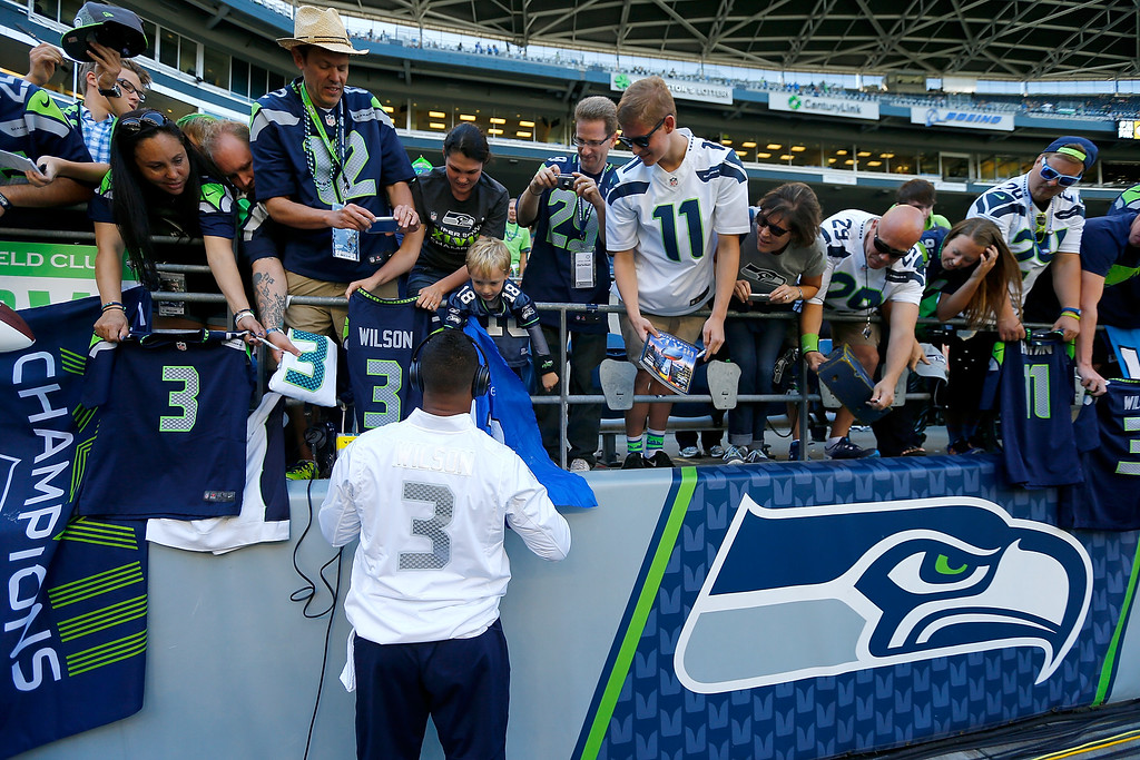 . SEATTLE - SEPTEMBER 04:  Quarterback Russell Wilson #3 of the Seattle Seahawks signs autographs before the game against the Green Bay Packers at Century Link Field on September 4, 2014 in Seattle, Washington.  (Photo by Jonathan Ferrey/Getty Images)