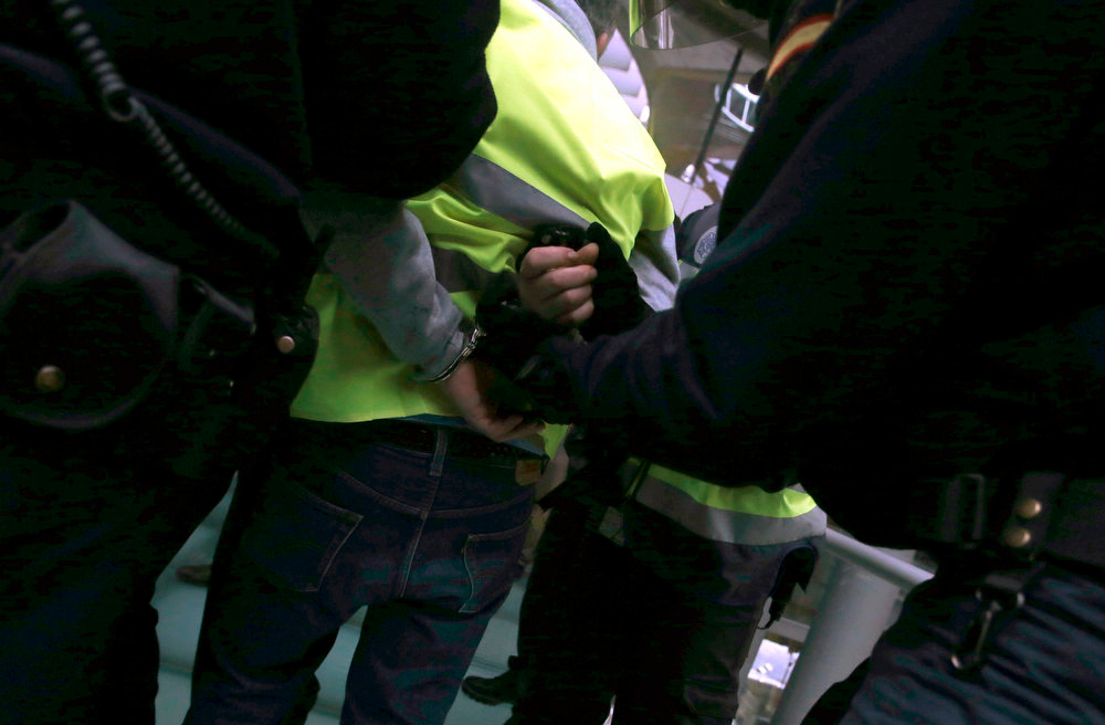 Description of . An Iberia worker is handcuffed by Spanish riot police officers during clashes at Madrid's Barajas airport February 18, 2013. Striking union workers clashed with police at Madrid's Barajas airport on Monday on the first day of a week-long strike over more than 3,800 pending job cuts at Spain's flagship airline Iberia. REUTERS/Sergio Perez