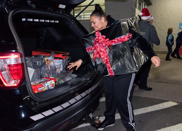 12/03/18 Wesley Bunnell | Staff The Bristol Police Explorers held their annual toy drive outside of Walmart on Monday evening. Police Explorer Destiny Guzman, a Bristol Eastern High School student, carries donated baby toys from a customer to place in back of the police cruiser.