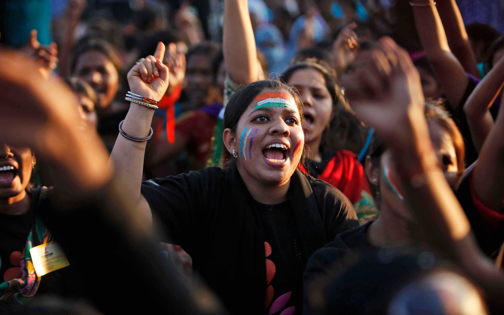 Description of . Indian women shout slogans during an event to support the