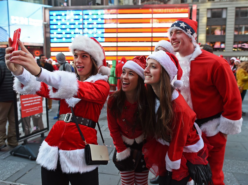 . Santas and Helpers take selfies in Times Square as hundreds of Santas gather for the annual Santacon festivities on December 13, 2014 in New York. AFP PHOTO/DON  EMMERT/AFP/Getty Images