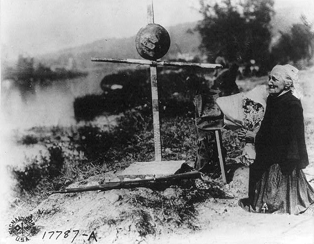 . Lest we forget. Elderly woman holding flowers and kneeling at grave of soldier, France, May 30, 1918. Courtesy the Library of Congress