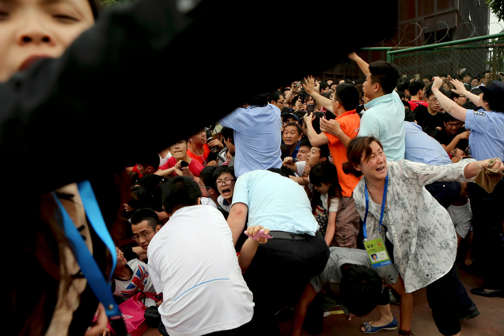 . A crowd reacts during a stampede by fans of David Beckham at a university in Shanghai on Thursday, June 20, 2013. Fans eager to the see the soccer superstar stormed a police cordon Thursday in a stampede at a Shanghai university that injured seven people including five security personnel. (AP Photo)