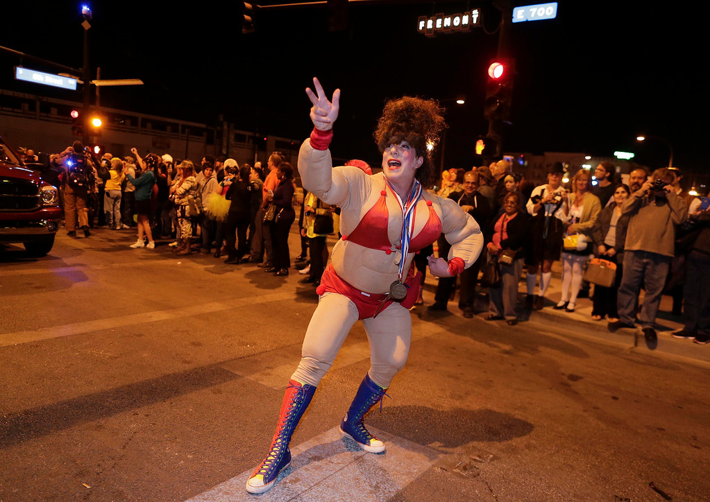 . A reveler dressed as a bodybuilder poses for spectators while walking in the fourth annual Las Vegas Halloween Parade, Thursday, Oct. 31, 2013, in Las Vegas. (AP Photo/Julie Jacobson)
