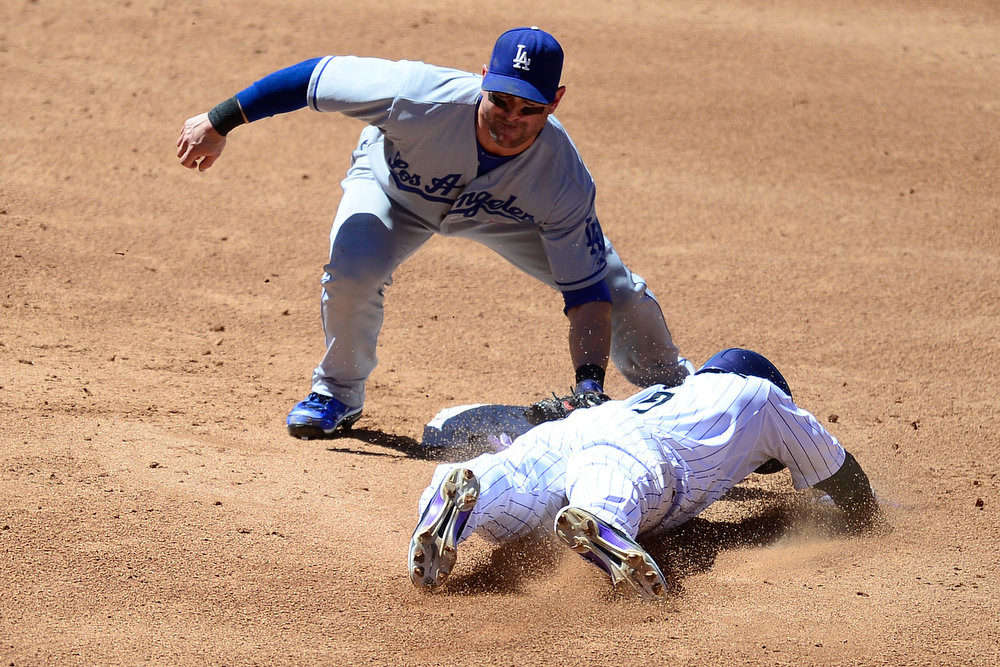 . Los Angeles Dodgers second baseman Nick Punto (7) tags out Colorado Rockies left fielder Carlos Gonzalez (5) as he attempts to steal second during action in Denver. The Colorado Rockies hosted the Los Angeles Dodgers at Coors Field. (Photo by AAron Ontiveroz/The Denver Post)