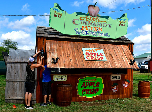 8/22/2019 Mike Orazzi | Staff Aaron Collomy and Thomas Hull while setting up the Apple Cinnamon Buns stand at the Terryville Country Fair while preparing for Friday's opening day.
