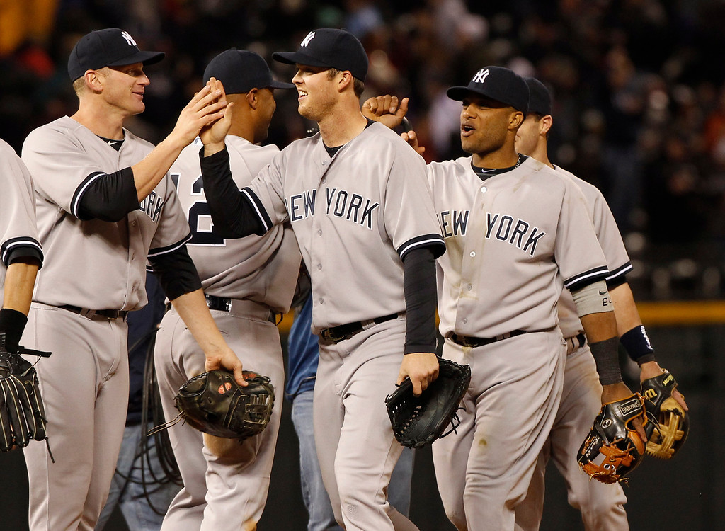 . New York Yankees\' Lyle Overbay, left, congratulates Brennan Boesch, center, as Robinson Cano looks on after their 3-2 win over the Colorado Rockies in a baseball game in Denver, Wednesday, May 8, 2013. (AP Photo/David Zalubowski)