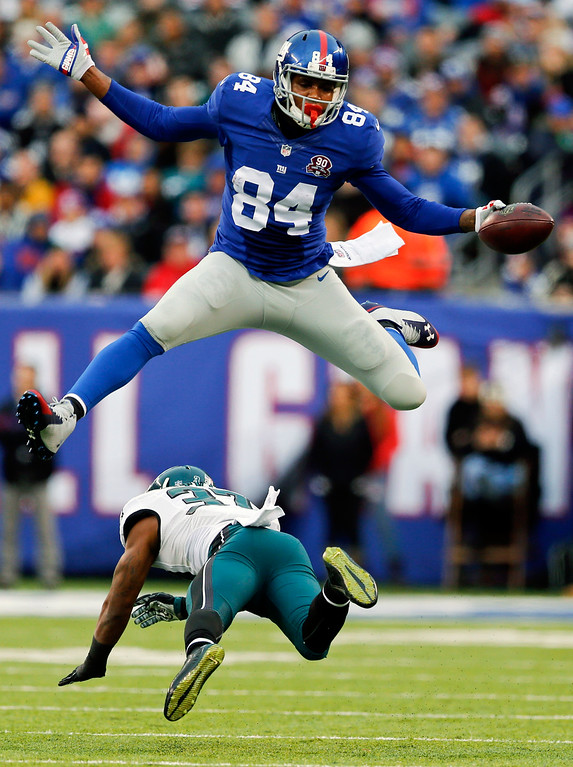 . New York Giants\' Larry Donnell (84) hurdles Philadelphia Eagles\' Jaylen Watkins (37) during the second half of an NFL football game Sunday, Dec. 28, 2014, in East Rutherford, N.J. (AP Photo/Julio Cortez)