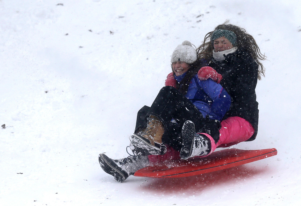 . Jamie Dustin, left, and Sarah Clarke go airborne as they sled down a hill, Thursday, Dec. 15, 2016, in Solon, Ohio. The day\'s high is expected to be 13 degrees as some schools in Northeast Ohio were canceled due to the weather. (AP Photo/Tony Dejak)