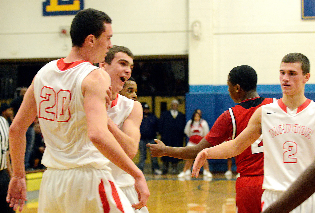 . Maribeth Joeright/MJoeright@News-Herald.com<p> Mentor\'s Kade McClure is congratulated by teammates Joey Zaugg, left, and Kyle Hagey after McClure\'s slam dunk during the Division I district final game against Glenville.