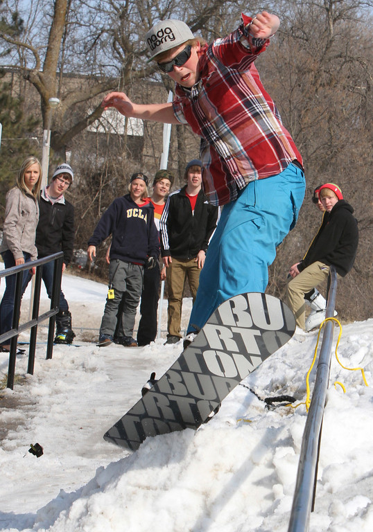 . Snow boarder Kyler Walczak jumps onto a rail Thursday, March 28, 2013 even as the snow in Brainerd, Minn. melted in the 40 degree temperature. (AP Photo/Brainerd Dispatch, Kelly Humphrey)