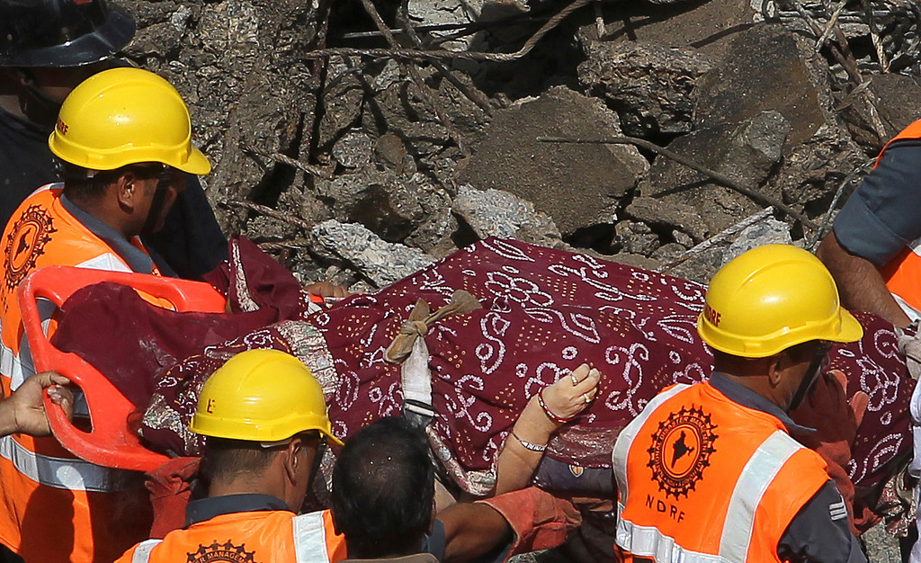 . Members of the National Disaster Relief Force take out the body of a woman from the debris of a collapsed building in Mumbai, India, Friday, Sept. 27, 2013.  (AP Photo/Rajanish Kakade)