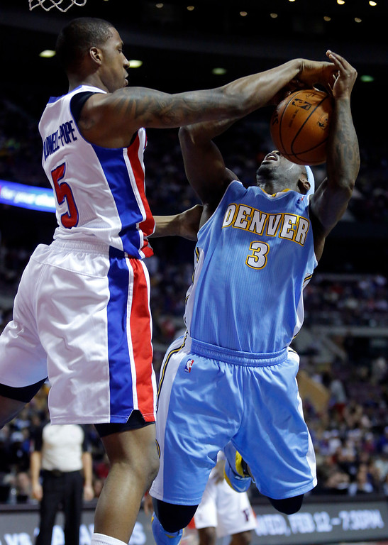 . Detroit Pistons guard Kentavious Caldwell-Pope (5) blocks a shot by Denver Nuggets guard Ty Lawson (3) during the first half of an NBA basketball game on Saturday, Feb. 8, 2014, in Auburn Hills, Mich. (AP Photo/Duane Burleson)
