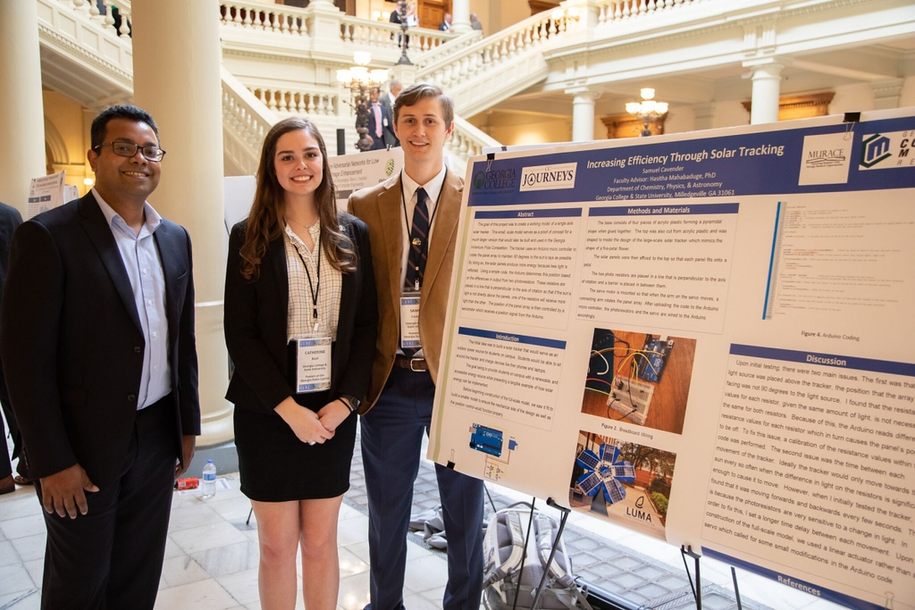 Mahabaduge with physics students Catherine Boyd and Bo Cavender at Posters at the Capital in January 2020.