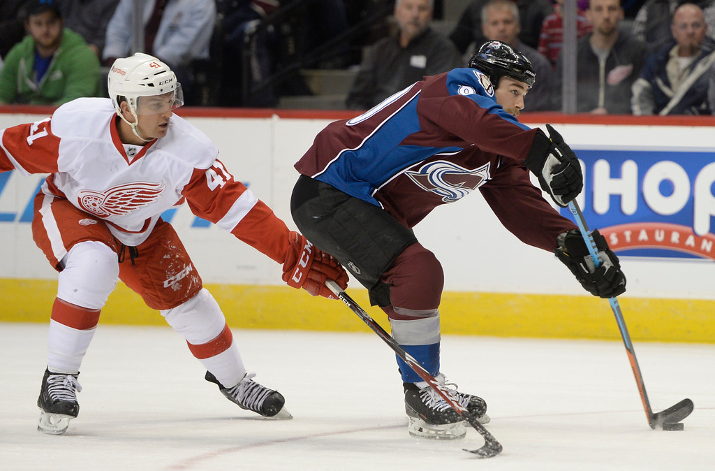 . DENVER, CO - February 5: Colorado Avalanche center Ryan O\'Reilly (90) sends a pass towards a team mate while being defended by Detroit Red Wings right wing Luke Glendening (41) during the first period Thursday, February 5, 2015 at the Pepsi Center in Denver, Colorado. (Photo By Brent Lewis/The Denver Post)