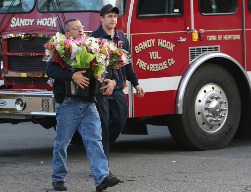 Description of . Volunteer firefighters carry flowers past their firetruck before placing them at a makeshift memorial near the Sandy Hook Elementary school Saturday, Dec. 15, 2012 in the Sandy Hook village of Newtown, Conn. The massacre of 26 children and adults at Sandy Hook Elementary school elicited horror and soul-searching around the world even as it raised more basic questions about why the gunman, 20-year-old Adam Lanza, would have been driven to such a crime and how he chose his victims. (AP Photo/Mary Altaffer)