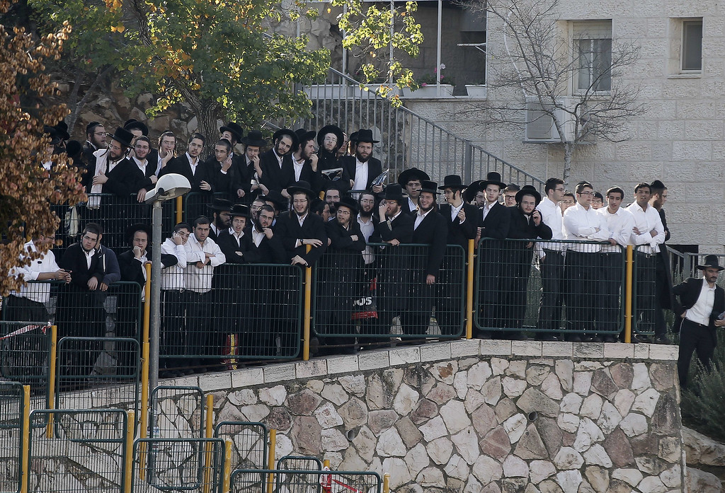 . Ultra-orthodox Jews watch emergency personnel (unseen) clean up and secure the area of an attack, by two Palestinians, on Israeli worshippers at a synagogue in the ultra-Orthodox Har Nof neighborhood in Jerusalem on November 18, 2014. AFP PHOTO /AHMAD GHARABLI/AFP/Getty Images