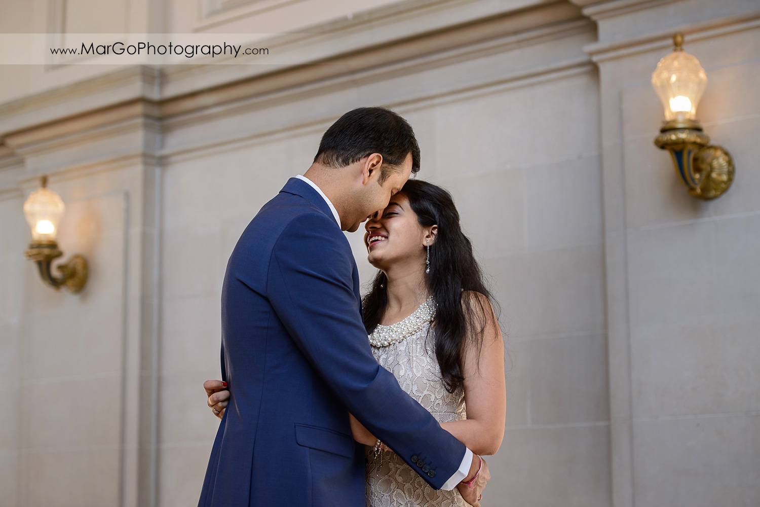 3/4 portrait of woman in beige dress and man in navy blue looking at each other on the fourth floor of San Francisco City Hall