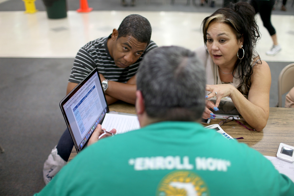 . HEALTHCARE: Jose Ramirez (L) and Mariana Silva speak with  Yosmay Valdivia, an agent from Sunshine Life and Health Advisors, as they discuss plans available from the Affordable Care Act at a store setup in the Mall of the Americas on December 15, 2014 in Miami, Florida. Today is the last day for people to sign up if they want insurance coverage under the Affordable Care Act to begin January 1, 2015.  (Photo by Joe Raedle/Getty Images)