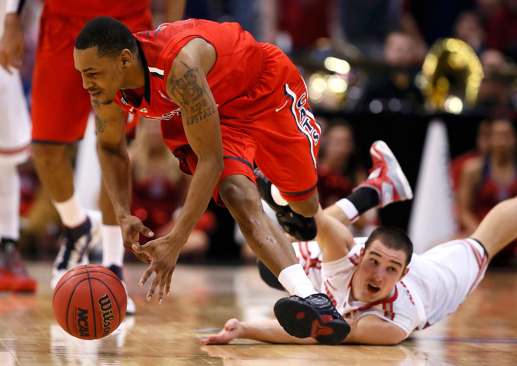 . Ohio State Buckeyes guard Aaron Craft (4) dives for a loose ball against Arizona Wildcats guard Mark Lyons (2) in their West Regional NCAA men\'s basketball game in Los Angeles, California March 28, 2013. REUTERS/Lucy Nicholson
