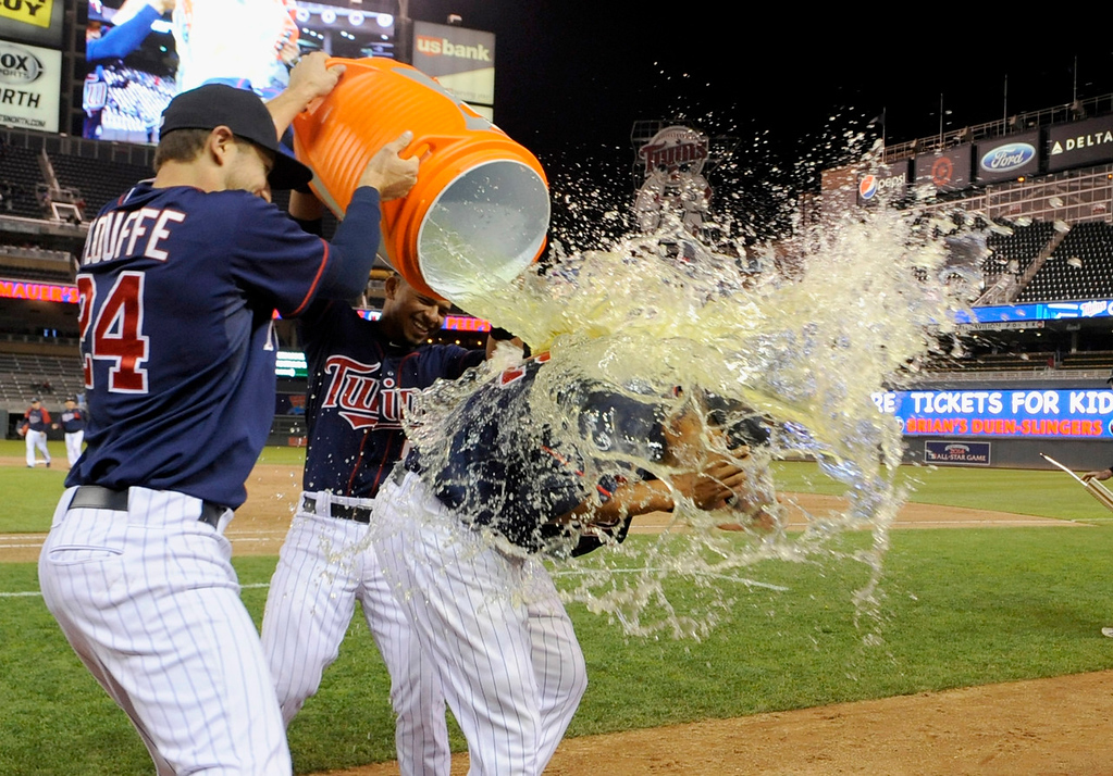 . Twins players Trevor Plouffe, left, and Eduardo Escobar soak teammate Aaron Hicks, right, with the traditional post-game bucket of Gatorade after Minnesota\'s 10-3 win over the Chicago White Sox on May 13, 2013 at Target Field in Minneapolis, Minnesota. (Photo by Hannah Foslien/Getty Images)