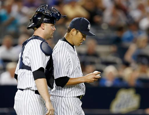 . New York Yankees catcher Brian McCann, left, talks to starting pitcher Hiroki Kuroda, who looks at the ball after Kuroda allowed a run-tying RBI single to Detroit Tigers Alex Avila in the seventh inning of a baseball game at Yankee Stadium in New York, Tuesday, Aug. 5, 2014.  (AP Photo/Kathy Willens)