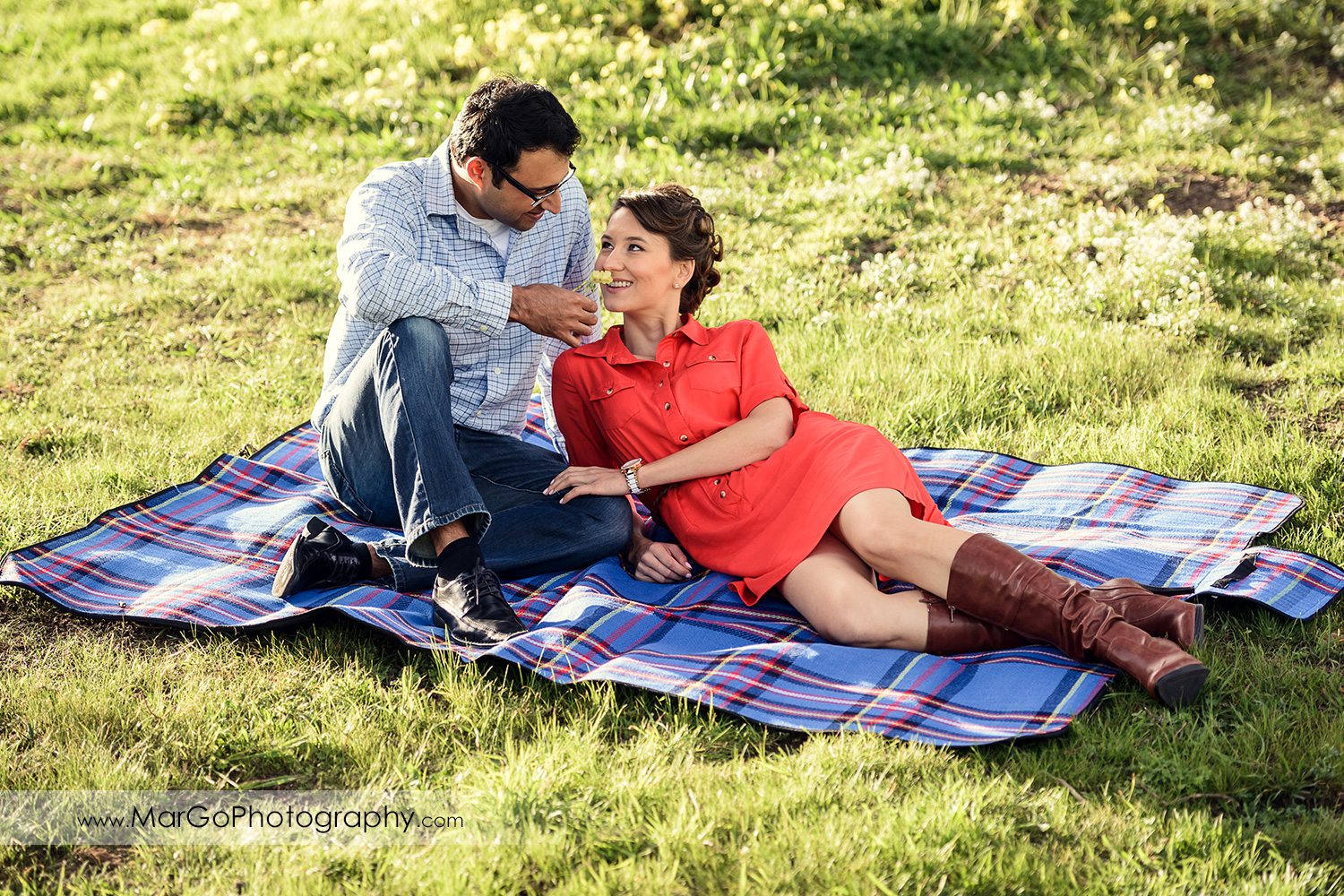 man in blue shirt and woman in red dress sitting on the blue blanket during engagement session at San Francisco Legion of Honor