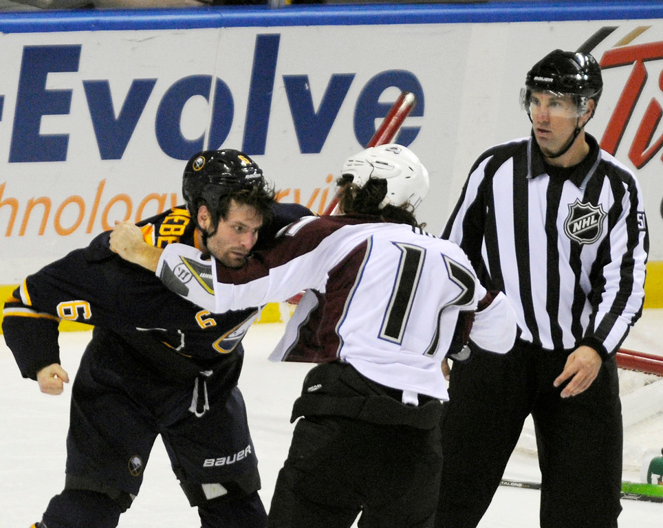 . Buffalo Sabres defensman Mike Weber (6) fights with Colorado Avalanche right winger Steve Downie (17) as NHL linesman Scott Cherrey (50) looks on during the third period of an NHL hockey game in Buffalo, N.Y., Saturday, Oct. 19, 2013. Colorado won 4-2.  (AP Photo/Gary Wiepert)