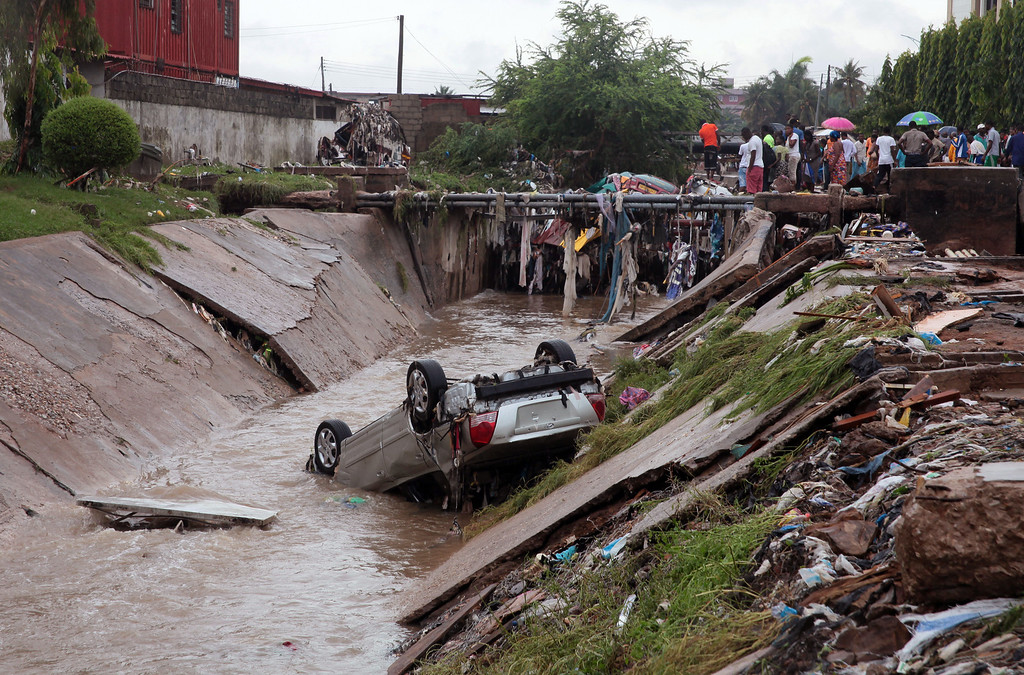 . A car lies in a water trench that washed away after heavy rain near a gas station explosion in Accra, Ghana, Thursday, June 4, 2015. Flooding in Ghana\'s capital swept stored fuel into a nearby fire, setting off a huge explosion at a gas station that killed scores of people and set alight neighboring buildings, authorities said Thursday. (AP Photo/Christian Thompson)