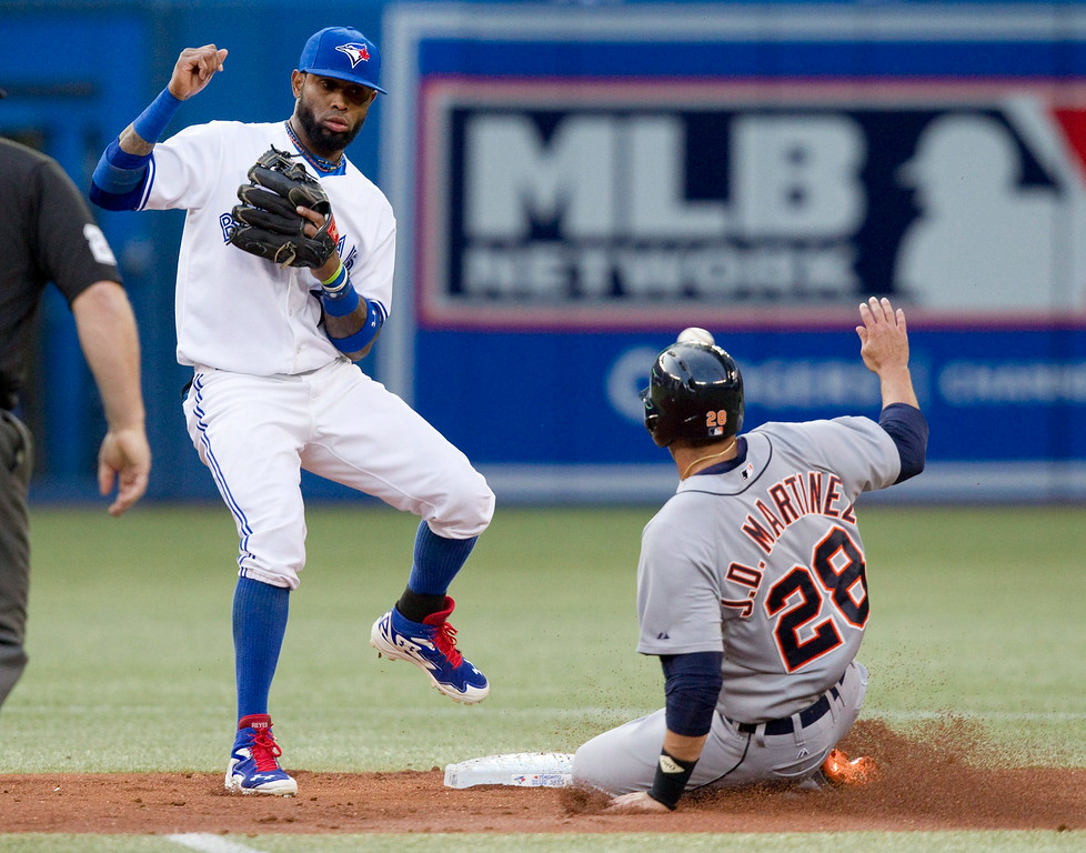 . Detroit Tigers\' Victor Martinez is safe stealing second base as the ball sails by Toronto Blue Jays shortstop Jose Reyes into center field during the second inning of a baseball game, Friday, Aug. 8, 2014 in Toronto. (AP Photo/The Canadian Press, Fred Thornhill)