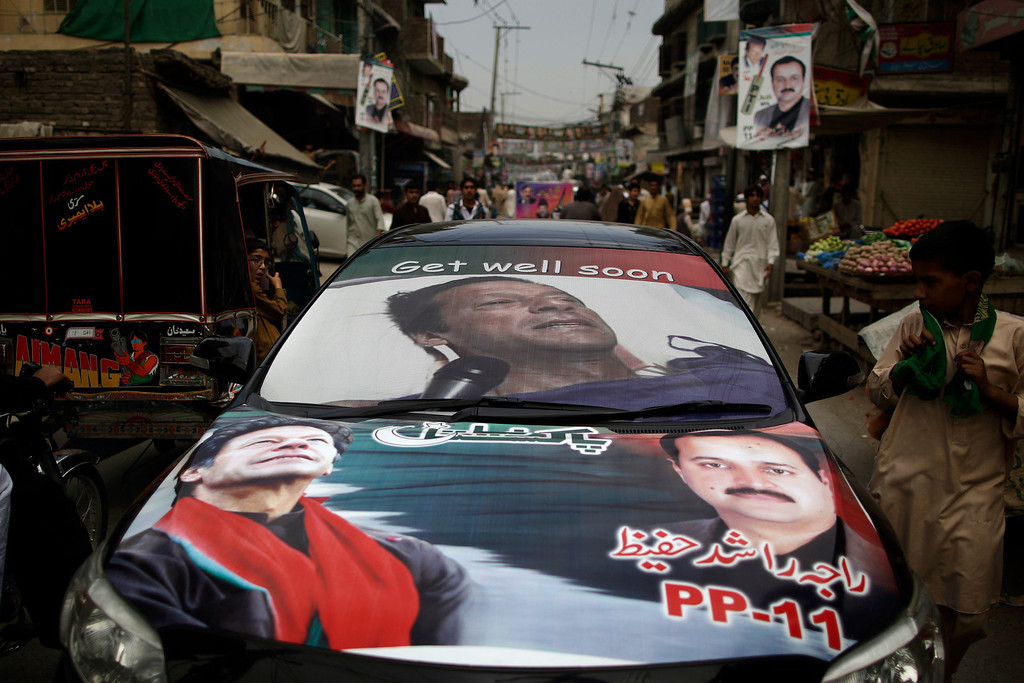 . Pakistani supporters of former cricket star-turned-politician, and leader of Pakistan Tehreek-e-Insaf party, Imran Khan, ride a car decorated with his Khan\'s pictures, near a polling station in Rawalpindi, Pakistan, Saturday, May 11, 2013. Defying the danger of militant attacks, Pakistanis streamed to the polls Saturday for a historic vote pitting a former cricket star against a two-time prime minister and an unpopular incumbent. But attacks that killed over a dozen people and wounded dozens more underlined the risks many people took just casting their ballots. (AP Photo/Muhammed Muheisen)