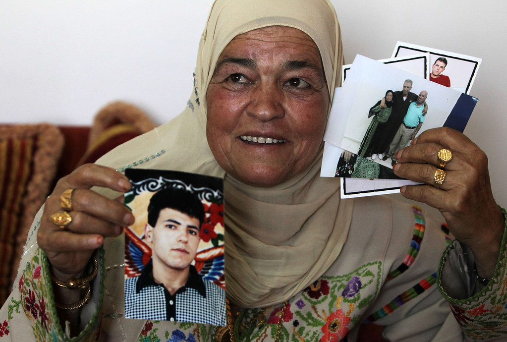 . Naamih Mansour, 60, holds pictures of her imprisoned son Esmat Mansour, in the West Bank village of Deir Jarir, near Ramallah, on August 13, 2013 as she prepares to celebrate his arrival home. Mansour is one of 26 Palestinian prisoners, most of them held for deadly attacks, Israel has agreed to release this week as part of a deal brokered by the United States, which led to the resumption of negotiations in the Middle East.  AFP PHOTO / ABBAS MOMANIABBAS MOMANI/AFP/Getty Images