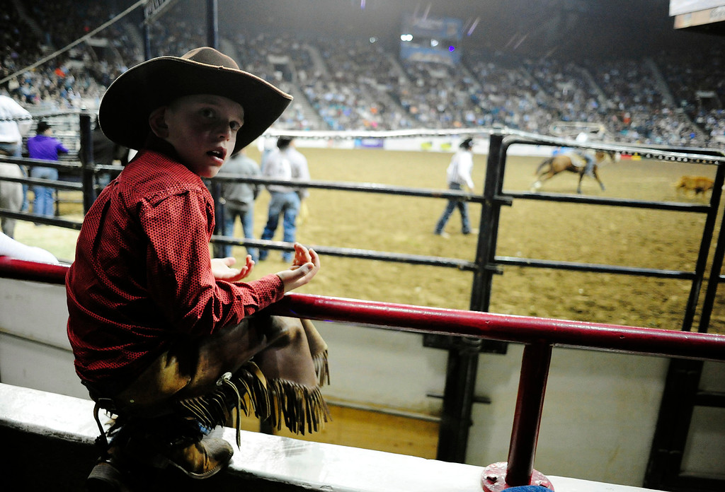 . Zachary Honn, 7, of Parker, CO, looks back towards his parents up in the stands behind him, during the U.S. Bank Pro Rodeo Finals, at the National Western Stock Show in Denver, CO, Sunday, January 26, 2014. Sunday was the final day of the event.  (Photo By Brenden Neville / Special to The Denver Post)