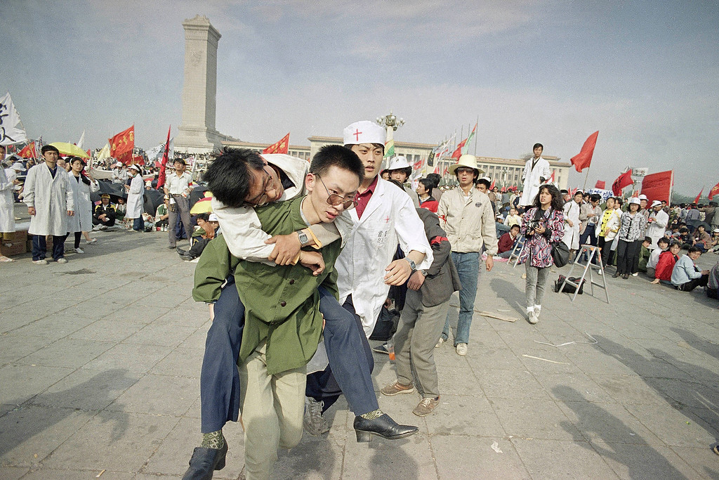 . In this May 16, 1989 file photo, medics rush a Beijing university student from Tiananmen Square after he collapsed on the third day of a hunger strike in Beijing. A quarter century after the Communist Party\'s attack on demonstrations centered on Tiananmen Square on June 4, 1989, the ruling party prohibits public discussion and 1989 is banned from textbooks and Chinese websites. (AP Photo/Sadayuki Mikami, File)