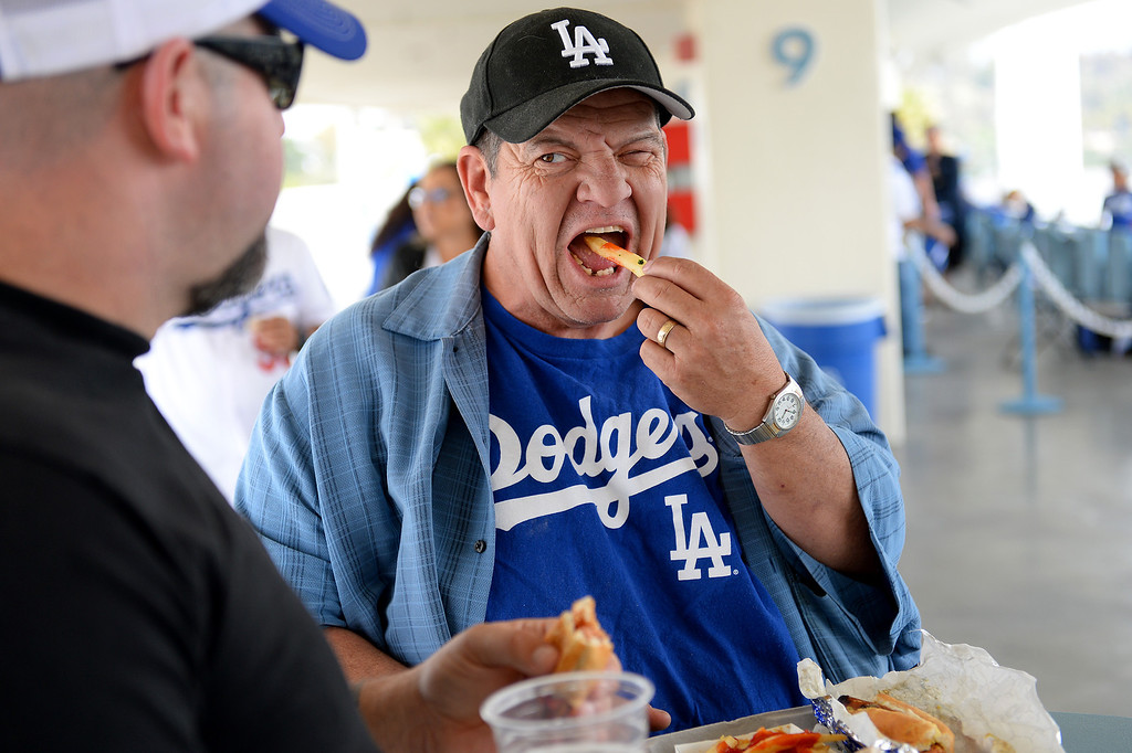 . Tim Wallen muches garlic fries and Dodger Dogs with his son Joe Wallen during at the Dodgers opener, Friday, April 4, 2014, at Dodger Stadium. (Photo by Michael Owen Baker/L.A. Daily News)