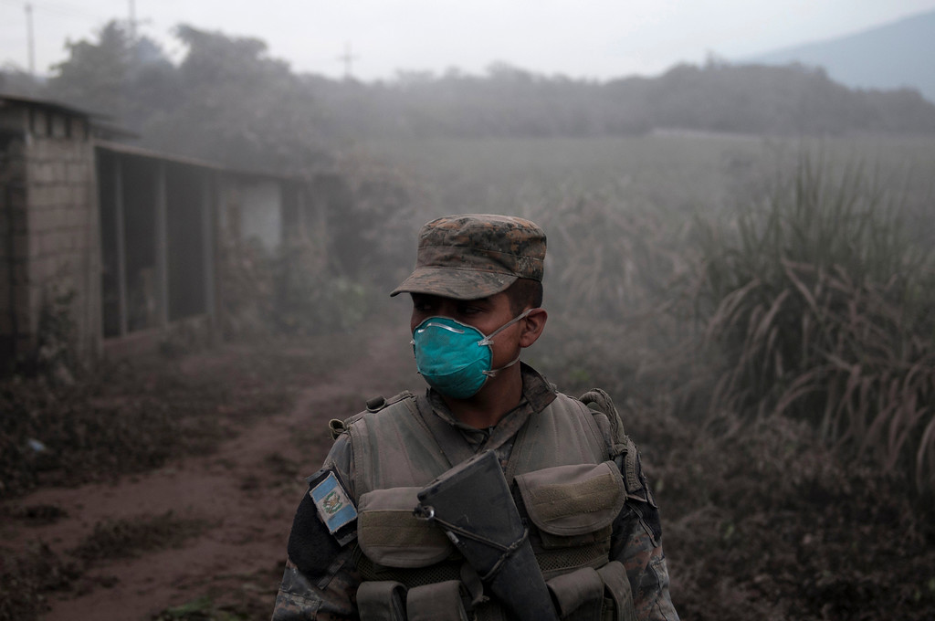 ". A soldier stands guard at a search and rescue site near the Volcan de Fuego, or ""Volcano of Fire,\"" in Escuintla, Guatemala, Monday, June 4, 2018. Rescuers have found the bodies of several more victims of an eruption at Guatemala\'s Volcano of Fire, and emergency workers have pulled some people still alive from ash drifts and mud flows. (AP Photo/Oliver de Ros)"